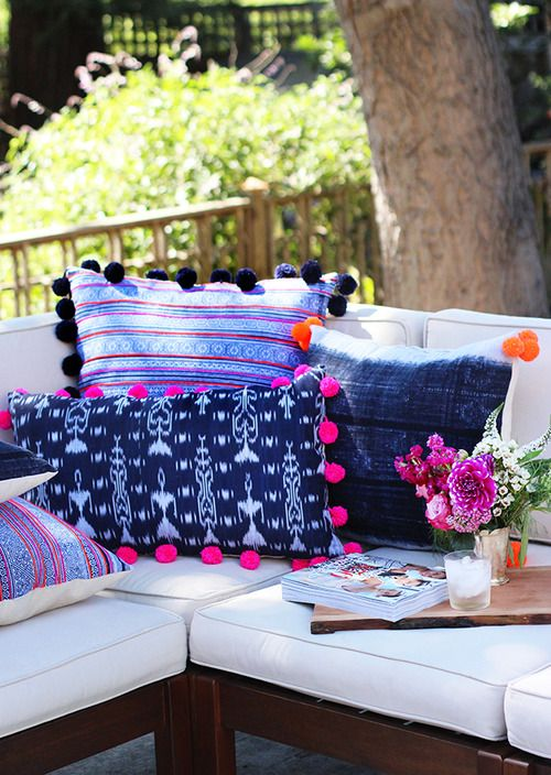 colorful printed pillows with a pompom trim for a cute look