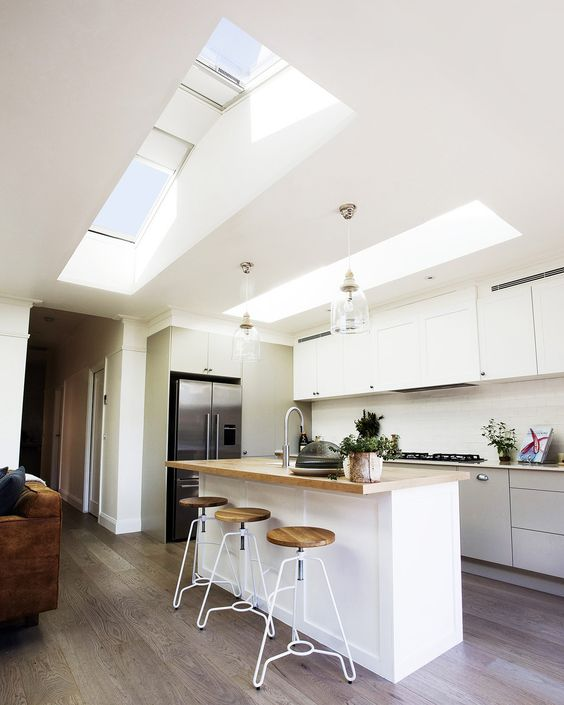 a minimalist white kitchen has no windows but there are two skylights to fill it with daylight
