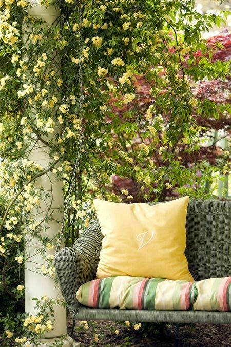 a rattan swing of a dark shade will stand out in the backdrop of gorgeous summer blooms