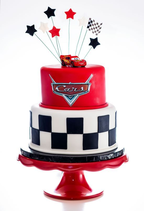 a red, black and white birthday cake with a proper topper and decor