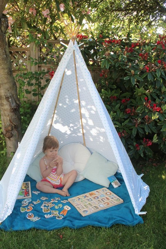 a small kids' teepee with a blue blanket and a polka dot cover, some soft pillows