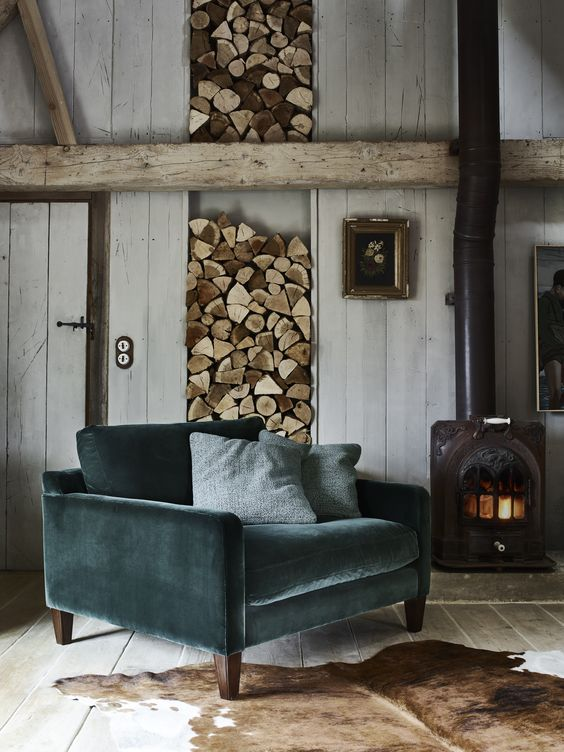 a teal velvet armchair will stand out in a rustic interior and will make sitting by the fire cozier
