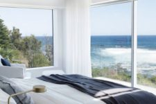 13 a white bedroom with a glazed wall and a large window, sea and forest views make the space enjoyable