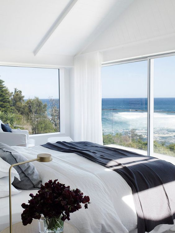 a white bedroom with a glazed wall and a large window, sea and forest views make the space enjoyable