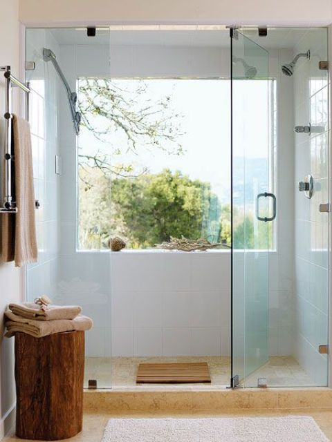 a woodland inspired shower with a large window that overlooks a forest, branches and rope for decor