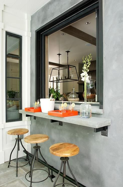 an industrial space with a concrete windowsill, metal and wood stools