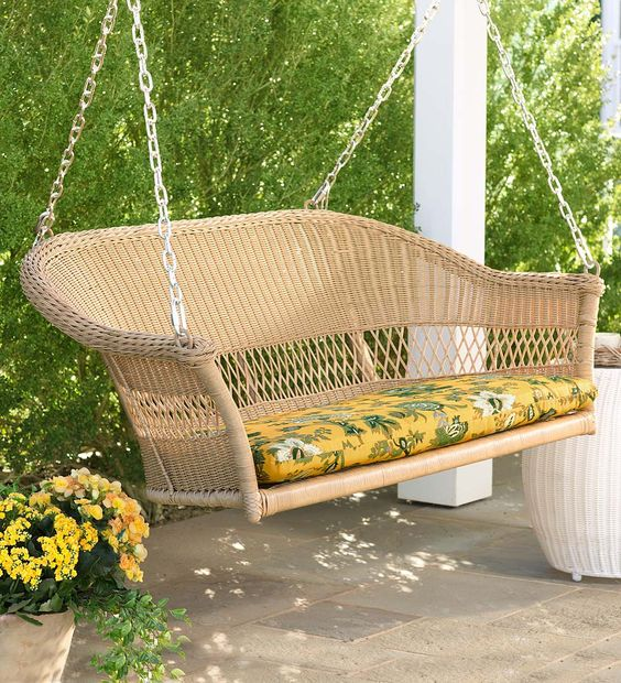 a resin wicker loveseat swing with a bold tropical print cushion to embrace the season