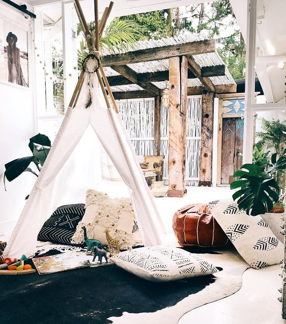 a small kids teepee with a dreamcatcher, covered with white and with cute pillows