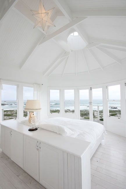a white bedroom with lots of windows and skylights that offer coastal views