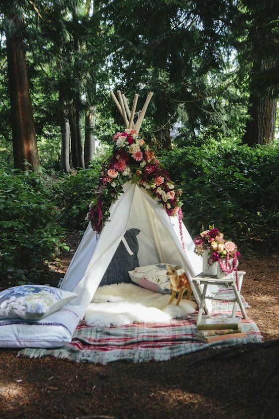 a small teepee of white fabric covered with lush florals, with blankets and pillows with a boho feel