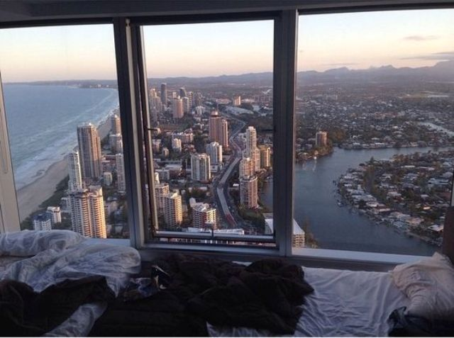 a window sill bed with the views of a big city and sea and beach views