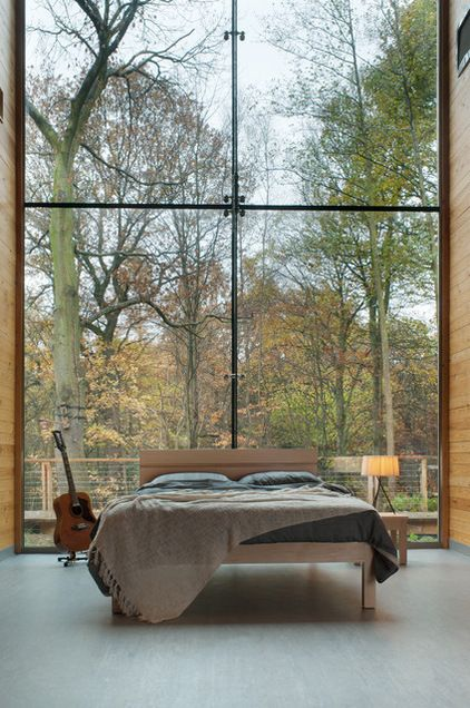 a large double height window instead of a headboard looks amazing and provides woodland views