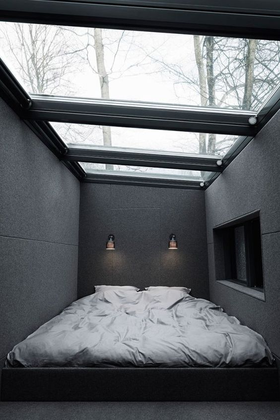 an ultra minimalist masculine bedroom with a glazed ceiling as a focal point of the space