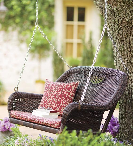 traditional brown wicker swing with a cushion is a great relaxing piece for any outdoor space