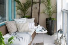 02 a balcony with a cozy daybed and many pillows, potted greenery and a small coffee table