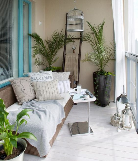 a balcony with a cozy daybed and many pillows, potted greenery and a small coffee table