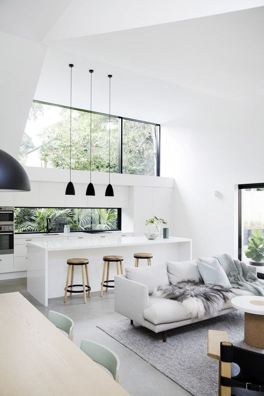 a minimalist white kitchen with a large skylight and a window backsplash with tropical greenery views