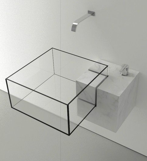 a modern sheer glass geometric sink with black framing on a marble holder