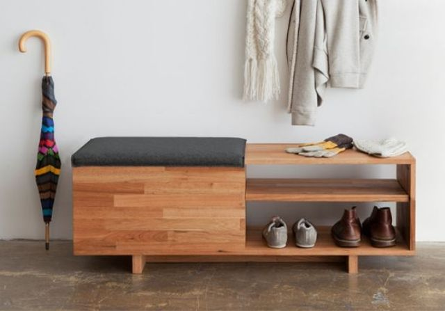 a modern wooden shelf with a drawer under the seat and open shelving is used as a bench