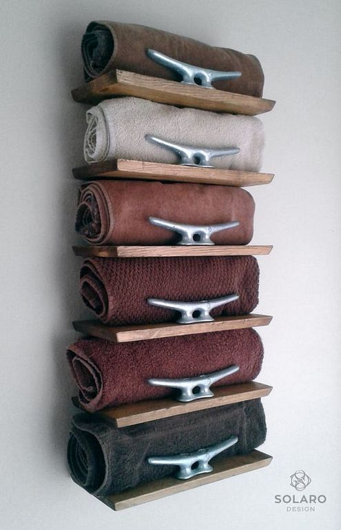 a tall narrow shelf on the wall won't take any floor space and will store many towels