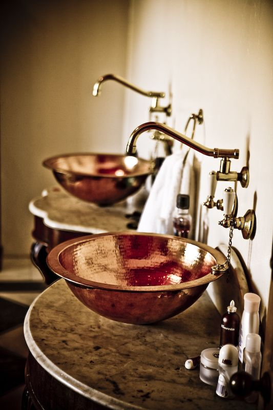 an industrial bathroom with shony hammered copper bowl sinks