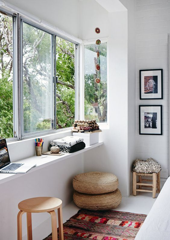 a boho chic balcony with a windowsill used for working and art