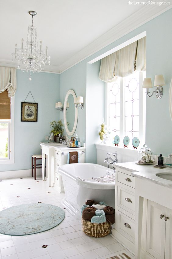 a coastal bathroom in light blue with a small glam chandelier to spruce it up