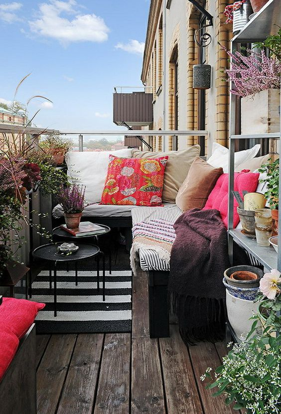 a cozy corner bench can be used for sleeping in the balcony, with colorful pillows and blankets