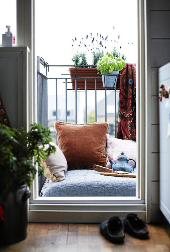 a large cushion with pillows on it are enough for reading on the balcony