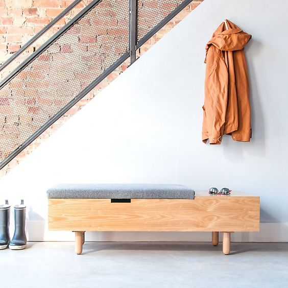 a modern wooden bench with a storage surface and grey seat, a sotrage space under it
