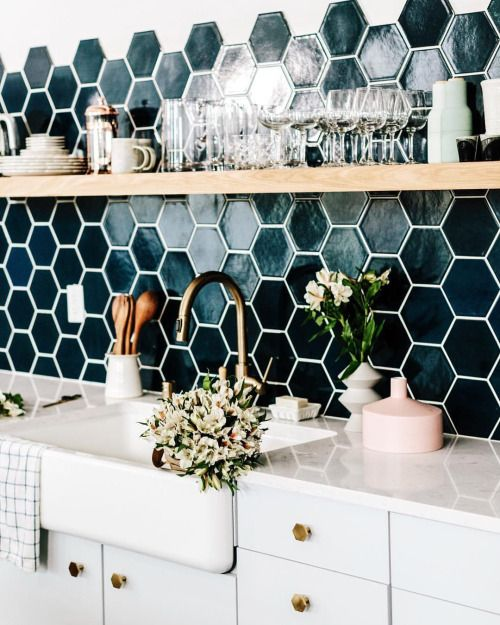 teal hexagon tiles with white grout add color to the white kitchen