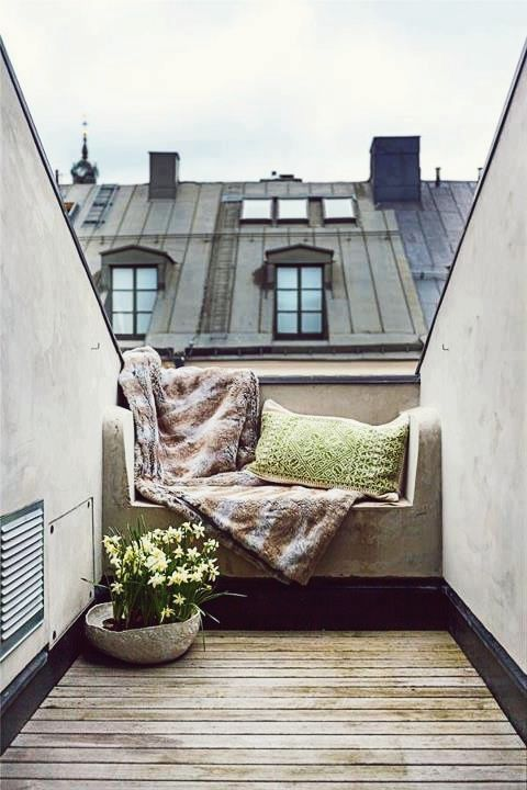 a concrete bench covered with blankets, pillows and cushions and potted flowers