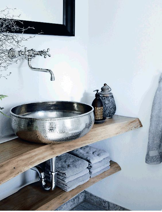 a gorgeous textural metal bowl sink contrasts a rough wood vanity and creates a bold look