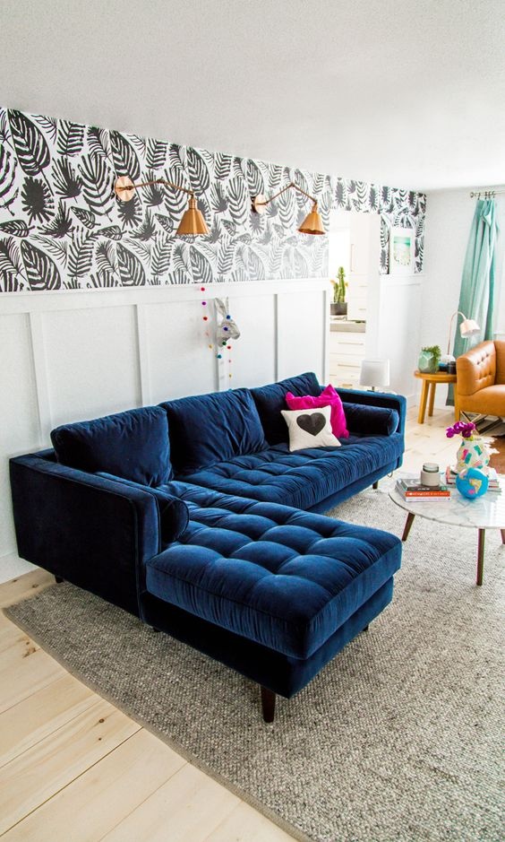 a navy modern velvet sofa is accentuated with contrasting pillows