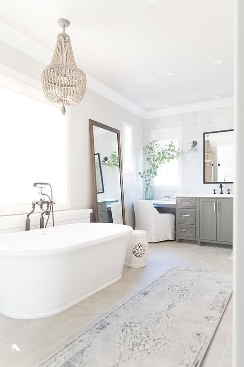 a neutral bathroom with a large mirror, a crystal chandelier and an armchair for a refined look