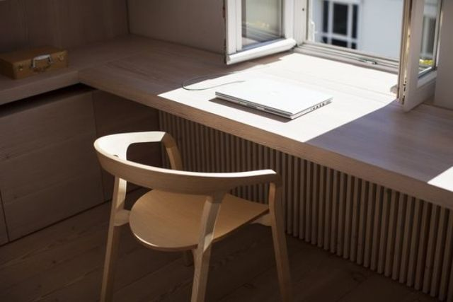 a sleek windowsill continued on the sides for a comfy modern workspace