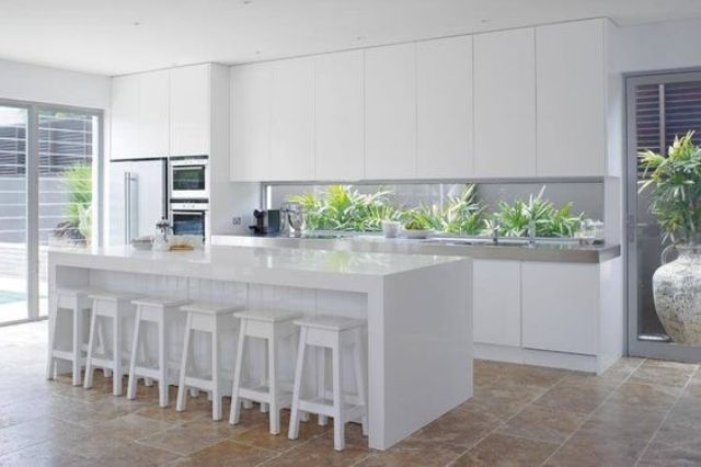 a minimalist white ktichen with a narrow window backsplash that shows greenery in the backyard