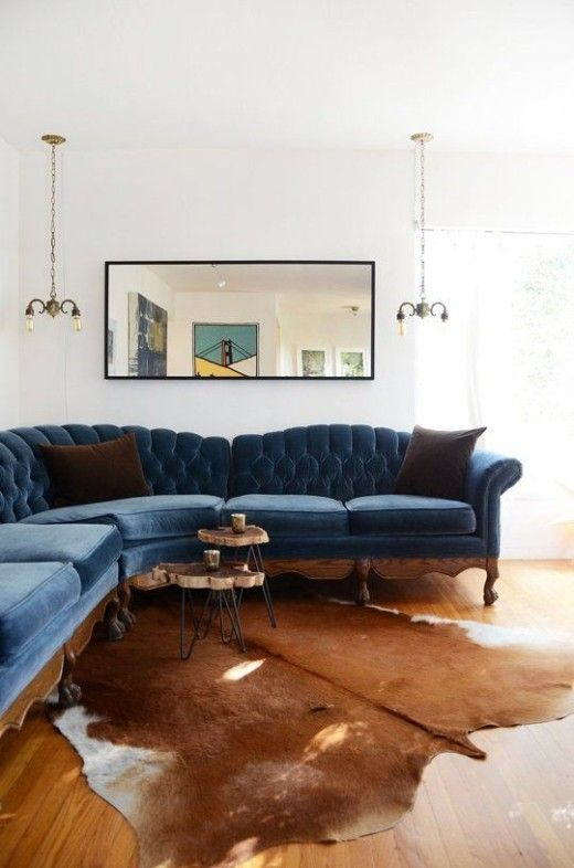 a navy velvet sofa on natural wood framing with a strong refined feel