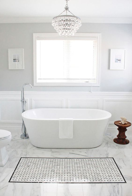 a peaceful bathroom in neutral shades with a large crystal chandelier and a free standing bathtub