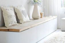 05 a white storage bench with a wooden top is a functional idea