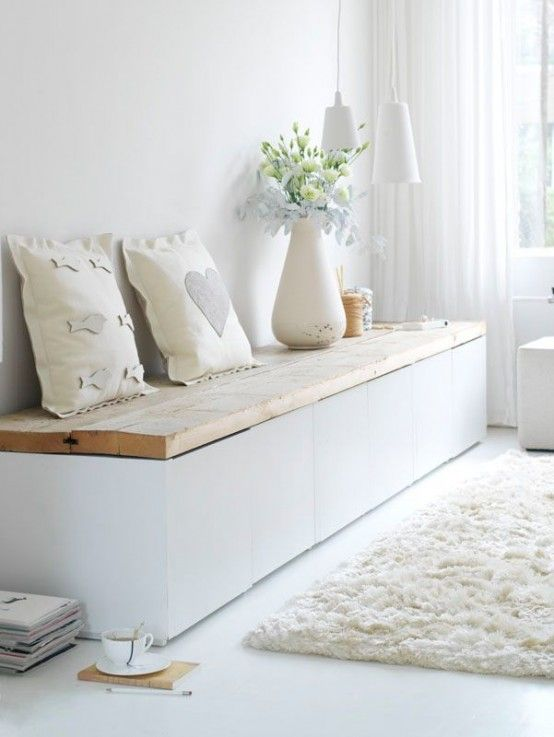 a white storage bench with a wooden top is a functional idea
