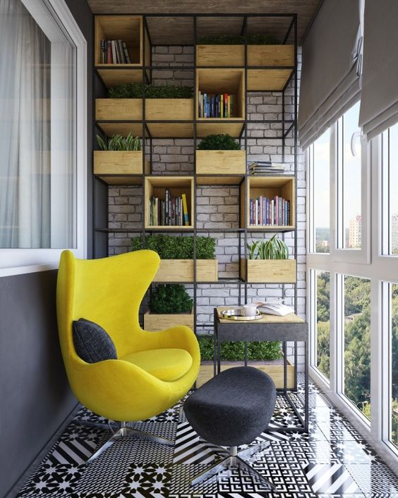 a cozy upholstered modern yellow chair with a graphite grey footrest and industrial shelving
