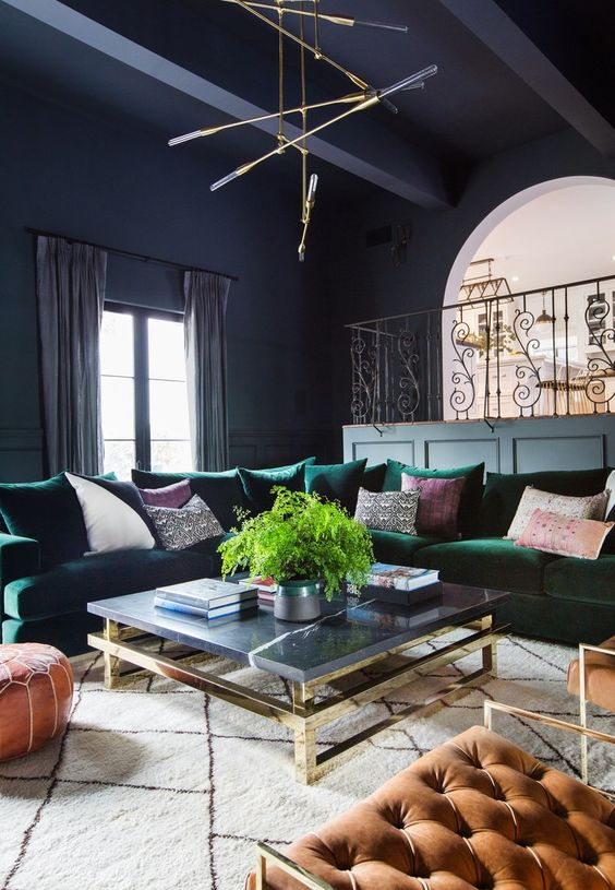 a dark space with a large emerald sectional sofa and brass touches
