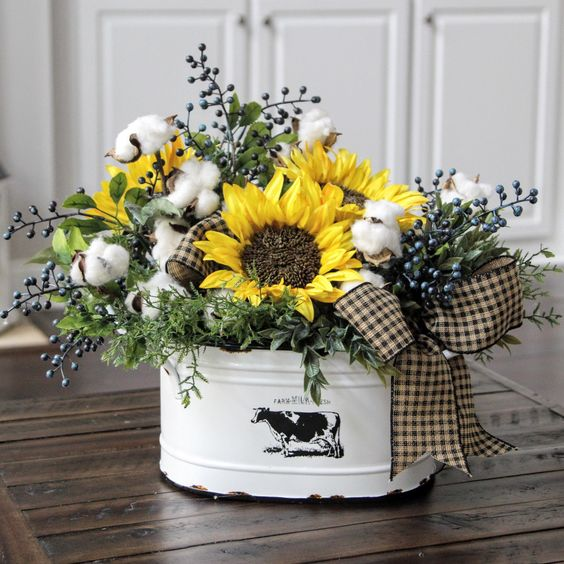 a metal bathtub with cotton and faux sunflowers plus a cute bow