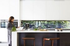 06 a modern black and white kitchen with a window backsplash that goes to the backyard