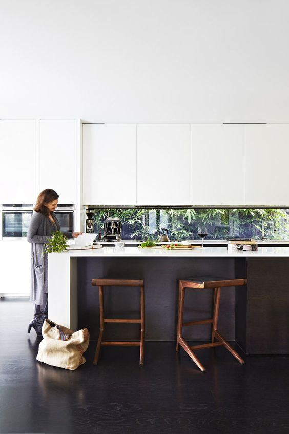 a modern black and white kitchen with a window backsplash that goes to the backyard