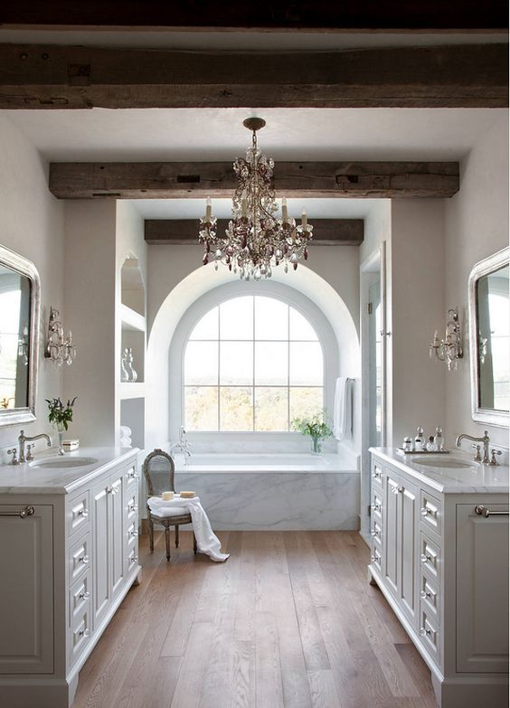 a refined farmhouse bathroom with woodden beams and a large chandelier