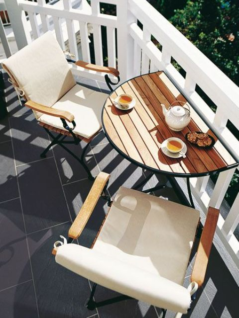a tiny balcony with a folding pallet table and a couple of folding chairs