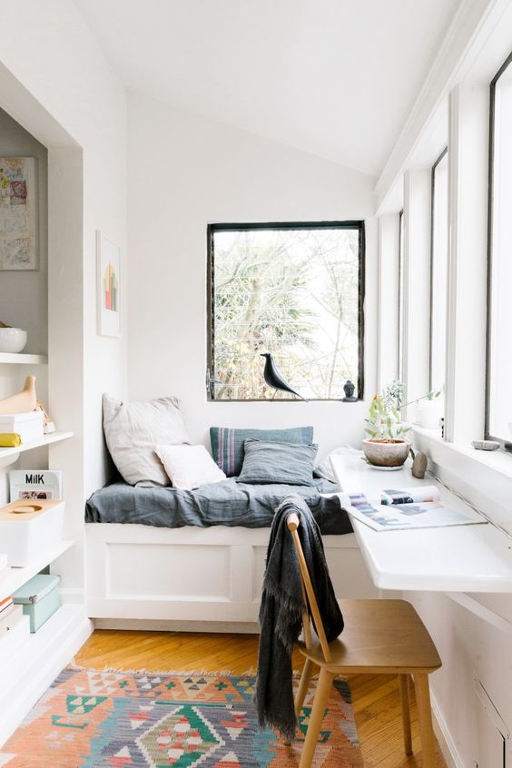 white balcony with a wooden floor, a daybed and a folding desk to study or work