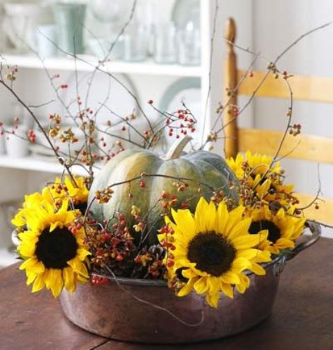 a bold arrangement with sunflowers, a pumpkin and berries